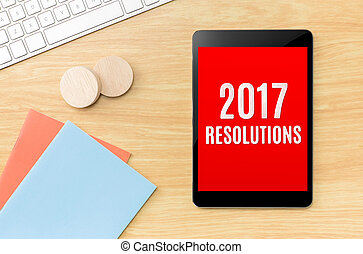 Top view of 2017 resolutions on screen tablet with blue...