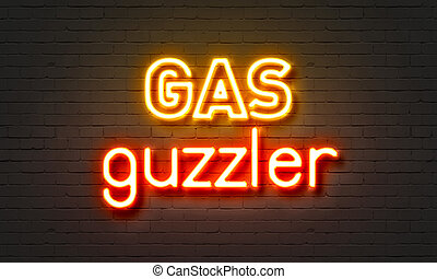 Gas guzzler neon sign on brick wall background. - Gas...