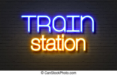 Train station neon sign on brick wall background.