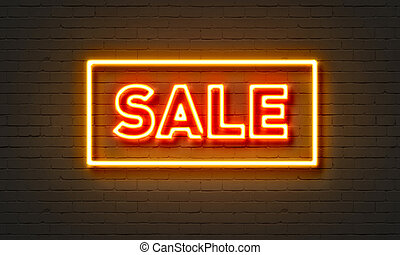 Sale neon sign on brick wall background.