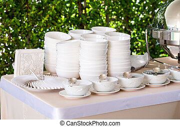 Ceramic white plate stacked on table for party in shady...