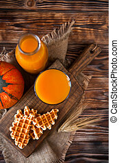 Bottle and Glass of fresh pumpkin juice with wafer and...