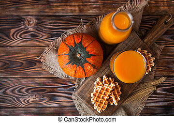 Bottle and Glass of healhty fresh pumpkin juice with wafer...