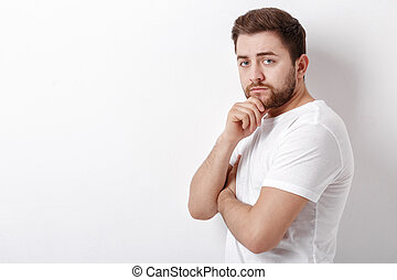 portrait of handsome young thinking man with beard ooking at...