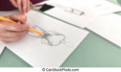 Designer sketching new dresses - Fashion designer sketching...