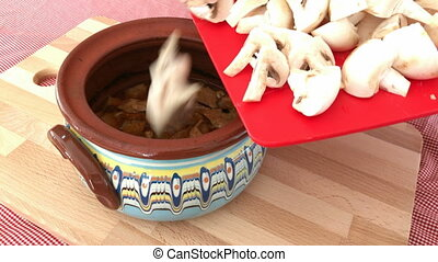 Meal with meat and mushrooms into gyuvetche pot - Preparing...