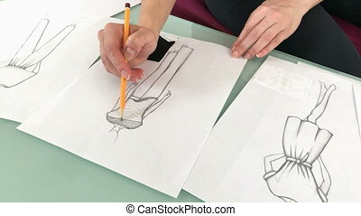 Sketching new dresses and models - Female fashion designer...