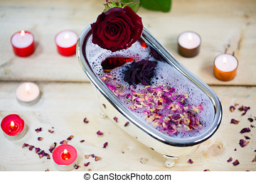 Bathtub filled with roses and rose petals, little bathtub