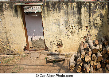 Indian village. Firewood stacked in pile in front of house...