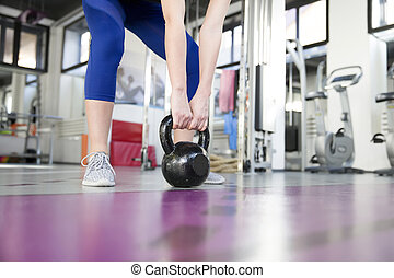 Young woman lifting weight in the gym