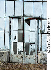 Door of abandoned greenhouse with paint on glass