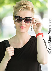 young woman with short blond hair and sunglasses