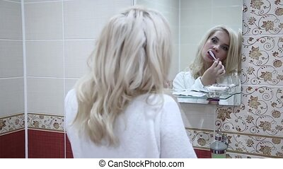sexy blondy woman brushing her teeth in the bathroom...