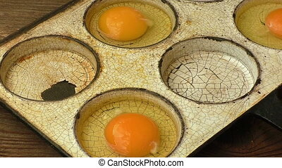 Eggs in old heavy duty steel frying pan isolated on wooden...