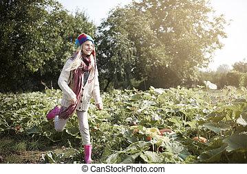 Girl running across the pumpkin field