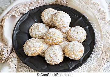 Coconut biscuits with icing sugar over pewter plate and...