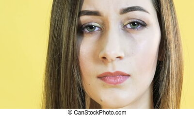 Cute woman with emotion of patience on yellow background....