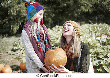 Woman with daughter have fun in the pumpkin field