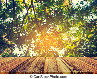 wood table and blur image of green tree bokeh. - wood table...