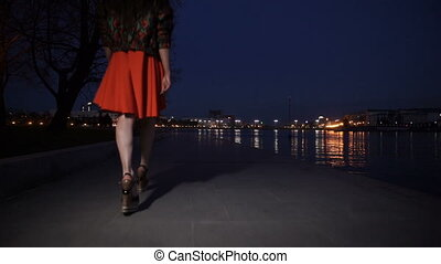 The girl in a red dress walking through the city along the...