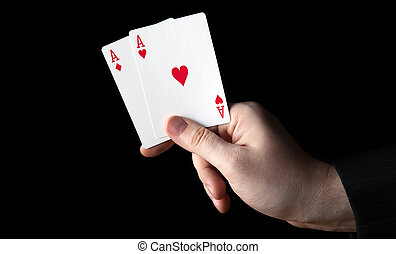 human hand holding two aces on a black background