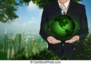 Young businessman holding Earth planet in hand. Elements of...