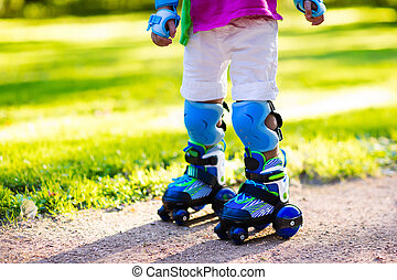 Kids roller skating in summer park - Little boy learning to...
