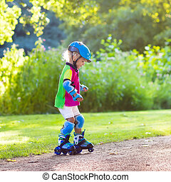 Kids roller skating in summer park - Little girl learning to...
