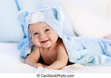 Baby in towel after bath in bed - Baby boy wearing diaper...