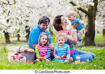 Family with children enjoying picnic in spring park - Big...