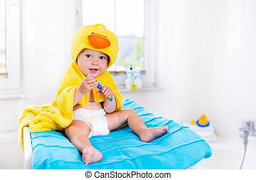 Baby in bath towel with tooth brush - Little baby in yellow...