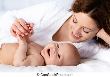 Baby and mother at home in bed. Mom and child. - Mother and...