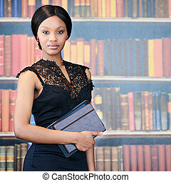 African woman standing in front of bookshelf with formal...