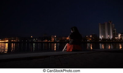 A girl sits on the railing of the night in the city