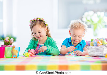 Kids with colorful Easter eggs on egg hunt - Kids painting...