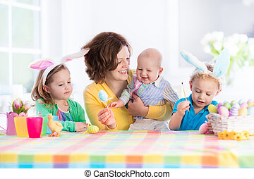 Mother with three children painting Easter eggs - Mother and...