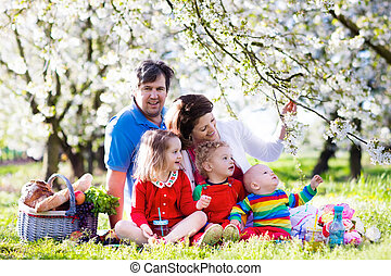 Family with kids on picnic in spring garden
