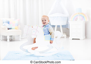 Baby boy in rocking horse toy - Cute baby boy riding wooden...
