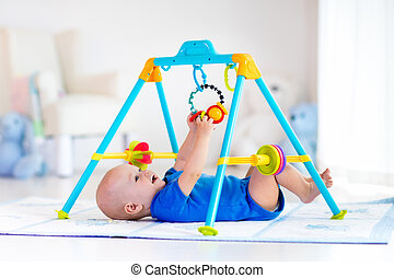 Baby boy on play mat. Child playing in gym. - Cute baby boy...