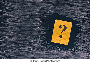 Yellow paper note with question mark on black board. Close...