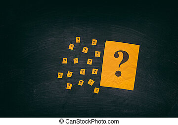Yellow paper notes with question marks on black board. Close...