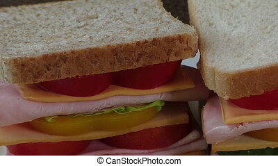 Close-up of two sandwiches with bacon, salami, prosciutto...
