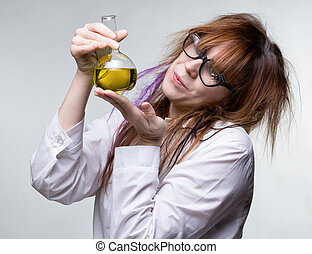Scientist woman with yellow liquid on gray background