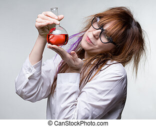 Scientist woman with red liquid on gray background