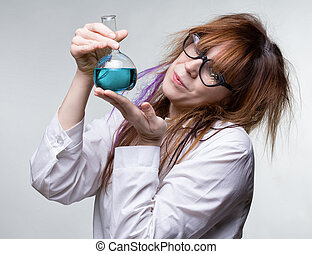 Scientist woman with blue liquid on gray background