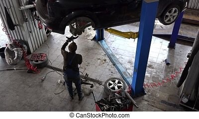 male mechanic repair lifted up automobile in car repair shop