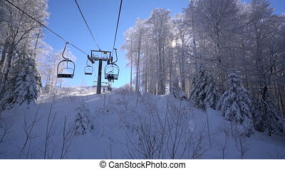 Snow forest and skiers on a ski lift pov