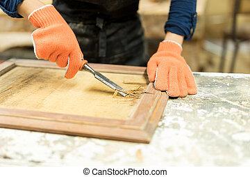 Carpenter using a wood gouge - Closeup of a female carpenter...