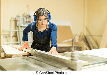 Female carpenter using a table saw - Portrait of a beautiful...