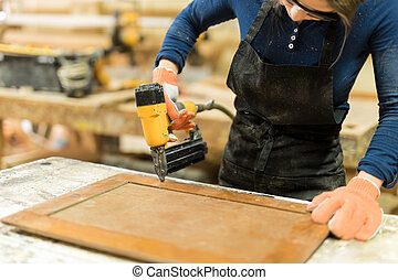 Woman using nail gun on some wood - Closeup of a young...
